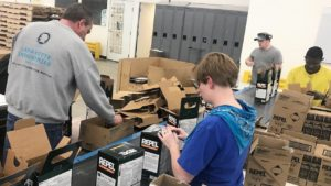 A team works together to package product.