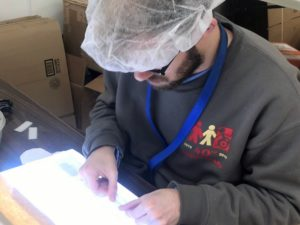 Employee uses a lightbox to build a product.