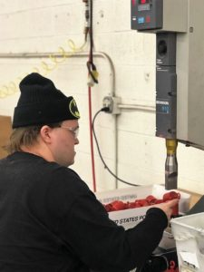 Employee uses a sonic welder to finsih building a product.