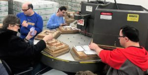 Employees working on a blister pack machine.